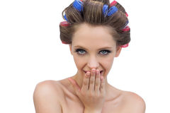 Signora secretiva in rulli dei capelli che posano esaminando macchina fotografica Fotografia Stock
