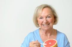 Signora senior in buona salute felice con un'arancia Immagine Stock