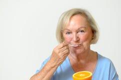 Signora senior in buona salute felice con un'arancia Fotografia Stock