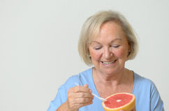 Signora senior in buona salute felice con un pompelmo rosso Fotografie Stock Libere da Diritti