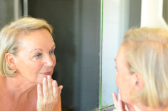 Signora senior che controlla la sua pelle nello specchio Fotografia Stock