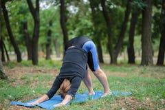 Signora senior che fa yoga su un fondo del giardino Addestramento duro di yoga Concetto di pratica di yoga Copi lo spazio Immagini Stock Libere da Diritti