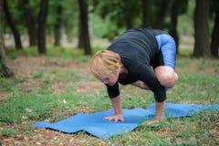 Signora senior che fa yoga su un fondo del giardino Addestramento duro di yoga Concetto di pratica di yoga Copi lo spazio Fotografie Stock Libere da Diritti