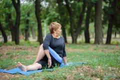 Signora senior che fa yoga su un fondo del giardino Addestramento duro di yoga Concetto di pratica di yoga Copi lo spazio Immagini Stock