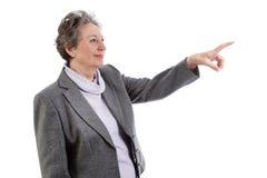 Signora senior che indica a qualcosa - donna più anziana isolata su briciolo Immagine Stock Libera da Diritti