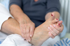 Signora senior che massaggia il suo piede immagini stock libere da diritti