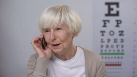 Signora senior che prende appuntamento con l'oculista, prevenzione relativa all'età di malattie video d archivio