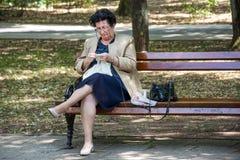 Signora senior che si siede sul banco in parco e che tricotta tovaglia immagini stock