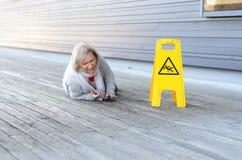 Signora senior che slitta e che cade su una superficie bagnata Fotografie Stock Libere da Diritti