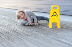 Signora senior che slitta e che cade su una superficie bagnata Fotografia Stock