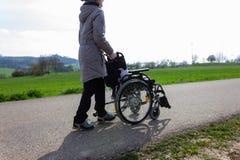 signora senior che spinge sedia a rotelle immagine stock