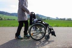 signora senior che spinge sedia a rotelle fotografia stock libera da diritti