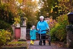 Signora senior con il camminatore che gode della visita della famiglia Immagini Stock Libere da Diritti