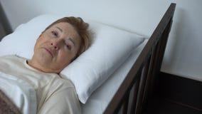 Signora senior malato terminale che grida e che esamina macchina fotografica, trovantesi nel letto del centro ospedaliero stock footage