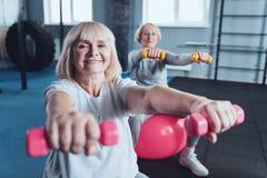 Signora senior occupata di positiva che gode dell'allenamento al club di forma fisica Fotografia Stock Libera da Diritti