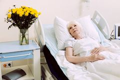 Signora senior pensierosa che si trova nel letto di ospedale Fotografie Stock