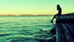 Signora Silhouette vicino alla spiaggia sul bacino di legno stock footage