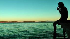 Signora Silhouette vicino alla spiaggia sul bacino di legno video d archivio