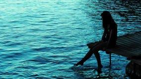 Signora Silhouette vicino alla spiaggia sul bacino di legno archivi video