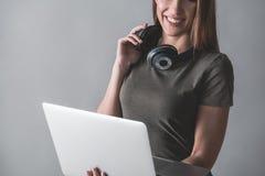 Signora soddisfatta che ascolta la musica sul computer Fotografia Stock