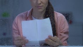 Signora sola turbata che si siede dietro la finestra piovosa e che legge lettera, famiglia mancante video d archivio