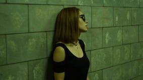 Signora sola in vetri ed in una maglietta nera sta vicino ad una parete in un sottopassaggio pedonale stock footage