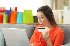 Signora sorpresa che compra online pagamento con la carta di credito fotografia stock