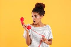Signora sorpresa che esamina microtelefono rosso isolato sopra giallo immagine stock