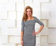 Signora sorridente bionda che sta vicino alla parete bianca futuristica Immagine Stock Libera da Diritti