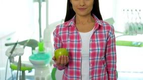 Signora sorridente che tiene mela succosa in ufficio dentario, vitamine per i denti sani fotografia stock