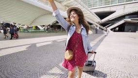Signora sorridente con la mano d'ondeggiamento dei bagagli stock footage