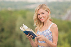 Signora sorridente con un libro all'aperto Fotografia Stock
