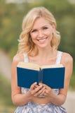 Signora sorridente con un libro all'aperto Immagine Stock Libera da Diritti