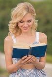 Signora sorridente con un libro all'aperto Fotografia Stock Libera da Diritti