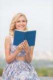 Signora sorridente con un libro all'aperto Immagini Stock Libere da Diritti