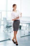 Signora sorridente dell'ufficio con il taccuino sul lavoro Immagine Stock
