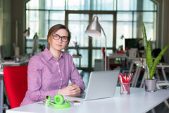 Signora sorridente di affari in abbigliamento casuale che si siede alla Tabella dell'ufficio Immagini Stock Libere da Diritti