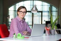 Signora sorridente di affari in abbigliamento casuale che si siede alla Tabella dell'ufficio Fotografie Stock