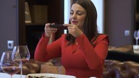 Signora sorridente elegante che si siede nel ristorante moderno La donna moderna prende la foto del suo alimento nel ristorante d stock footage