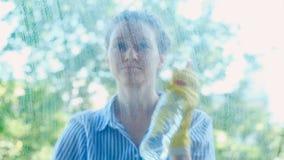 Signora sorridente nel detersivo degli spruzzi della camicia sulla finestra e sulle strofinate video d archivio