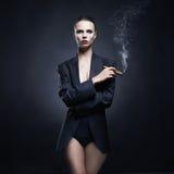 Signora splendida fuma Immagine Stock