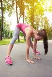 Signora sportiva che allunga le gambe durante l'allenamento nel parco Immagini Stock