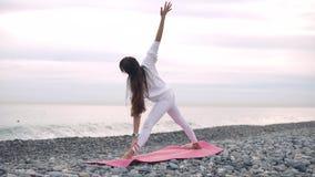 Signora sta facendo gli esercizi fisici sulla costa del ciottolo del mare di giorno stock footage