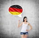 Signora sta precisando la bolla di pensiero con la bandiera della Germania dentro Fondo concreto Fotografie Stock