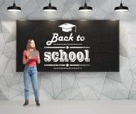 Signora sta riflettendo circa il prossimo anno accademico Parole: 'di nuovo alla scuola' sono scritti sulla lavagna nera Immagini Stock