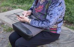 Signora sta utilizzando uno smartphone fotografia stock