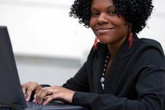 Signora sui sorrisi del calcolatore Fotografia Stock Libera da Diritti