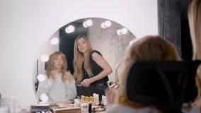 Signora sulla sedia e giovane donna vicino allo specchio archivi video
