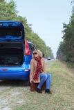 Signora sveglia che si siede con le valigie sulla strada vicino all'automobile blu Fotografie Stock