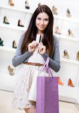 Signora tiene la carta di credito nel negozio delle calzature Fotografia Stock